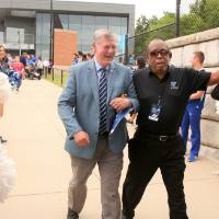 President Tom Haas walking arm-in-arm with a guest at the Jamie Hosford Football Center dedication.